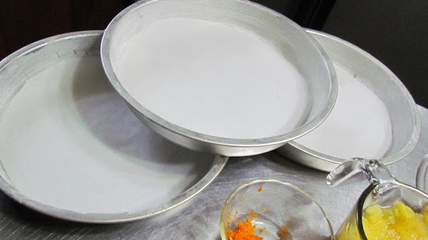 Grease and flour 3-9 inch round baking pans. Line the bottoms with parchment paper. Combine...