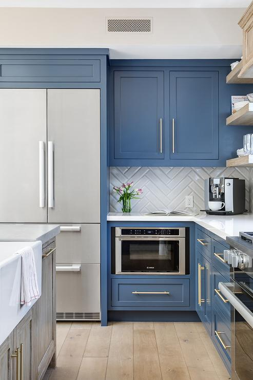 kitchen with blue shaker cabinets, stainless steel appliances, white herringbone backsplash and light wood floors