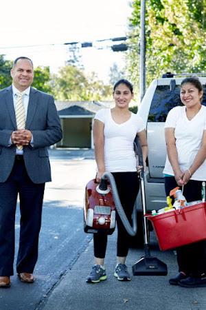 Three of Roses Cleaning Corporation employees pose outside for a photo with the tools of their trade.