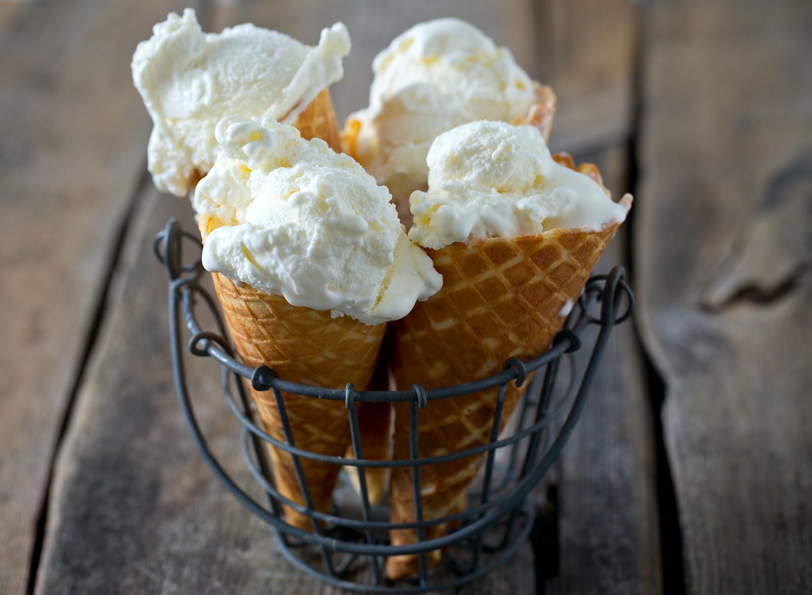 four vanilla ice cream cones in a wire holder