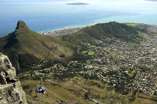 A view of the cablecar, Lion's Head, Signal Hill and Cape Town from Table Mountain with Robben Island in the distance. File photo