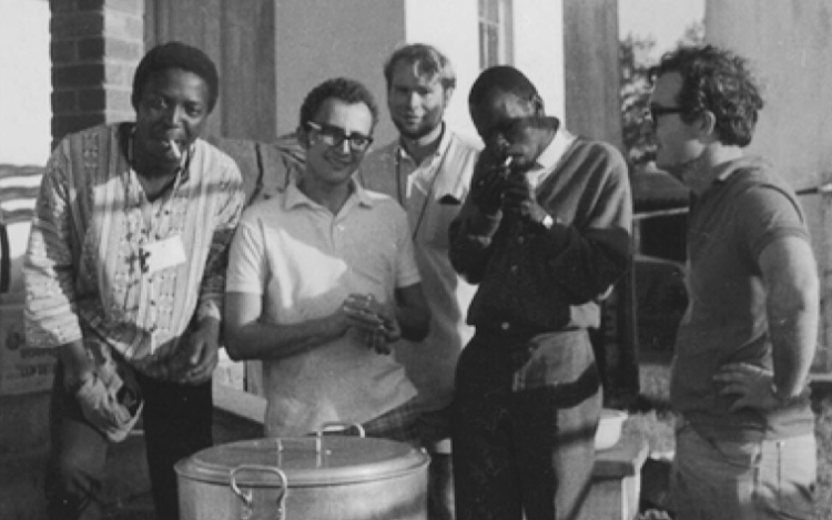 Steve Biko lighting up with Rick Turner (right), Dave Turnbull (centre) and volunteers who were helping restore the Mahatma Gandhi Ashram in Phoenix outside Durban in 1971.