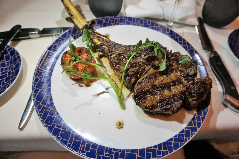 A bone-in Tomahawk rib eye steak entrée at Cagney's Steakhouse on Norwegian Getaway.