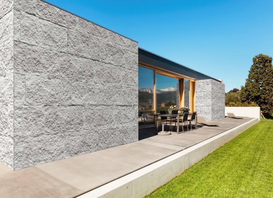 Fachada do fundo de casa com gramado, paredes revestidas de pedras naturais cinza, porta envidraçada e mesa com 4 cadeiras.