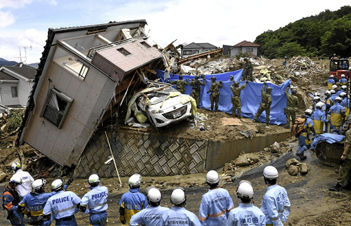 Rescue workers look for missing people in a house damaged by heavy rain, in Kumano in Japan's Hiroshima prefecture, on July 9 2018. Picture: KYODO VIA REUTERS