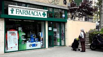 Una mujer espera a entrar a una farmacia durante el estado de alarma.