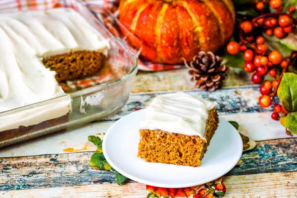 Slice Of Pumpkin Spice Cake With Cream Cheese Icing On A Plate.