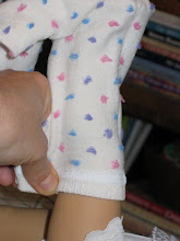 Photo: With your doll laying on her back, hold her leg up so her foot is in the air.  Pinch the sock at the back of her leg so it fits comfortably.   You want it snug but not too tight.   If you pull it too tight, it will distort the pattern on the sock.