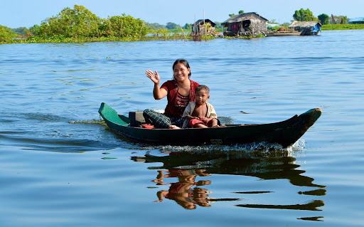 A mother and her son head to the local school in a flat bottom boat in Vietnam.