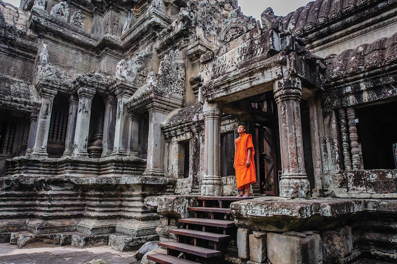A monk looks out from an ancient compound at Angkor Wat, Siem Reap, Cambodia.