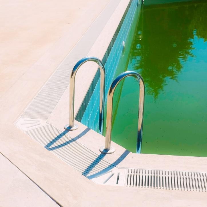 white metal pool ladder beside swimming pool