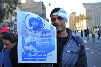 Photo: A protester holds up a poster identifying one of the soldiers implicated in the attacks.