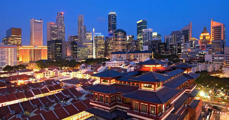 Traditional Asian historic buildings are offset by the modern Singapore skyline in the background.