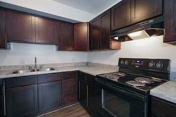 Close up of apartment kitchen with black appliances and dark wood cabinets