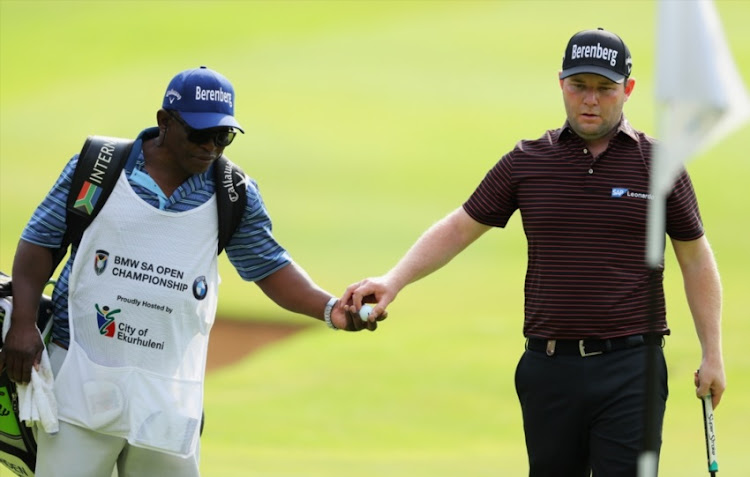 Branden Grace of South Africa passes a ball to caddie Zak Rasego on the 17th green during Day One of The BMW South African Open Championship at Glendower Golf Club on January 11, 2018 in Johannesburg.