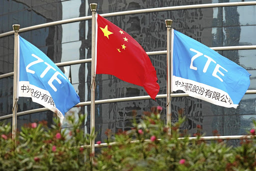 A Chinese national flag and two flags bearing the name of ZTE fly outside the ZTE research and development building in Shenzhen, China. Picture: REUTERS/Bobby Yip