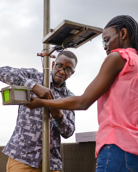 Engineer and a teammate installing a sensor on a rooftop in busy Kampala