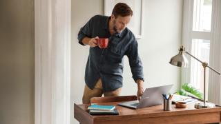 un hombre de pie escribiendo en un portátil