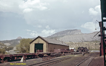 Photo: 077-36.  View of old car shop and Class K-36 engine #487.  Edge of coaling tower is at far right with the sand house a little further away along the track.  The silver colored truss bridge visible just above the top of the flat car at left was the bridge used by the RGS on its way to Hesperus and Mancos.  Track remained on it at this time so the D&RGW could serve the smelter across the Animas River.  Perins Peak in the background.  7/28/60.