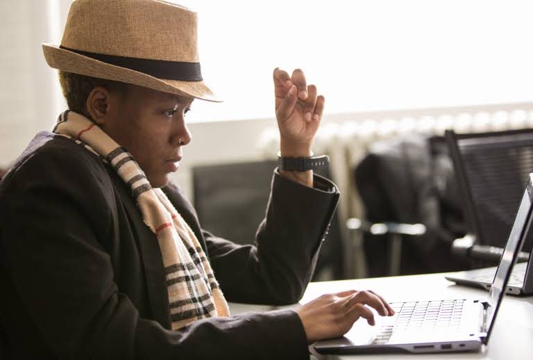 Young black educator in a hat and scarf in front of laptop.