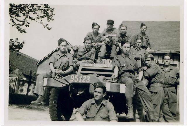 Rafael Gómez, abajo, ante el vehículo militar, con algunos de sus compañeros de La Nueve