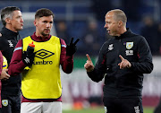 Burnley midfielder Danny Drinkwater with assistant manager Ian Woan during the warm up before the match in December 2019 at Turf Moor in Burnley. The club has confirmed that Woan will self-isolate at home for seven days after testing positive for Covid-19.