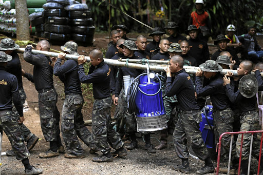 Thai military personnel carry a water pump as they enter the Tham Luang cave complex, where 12 boys and their soccer coach are trapped, on July 6 2018. Picture: REUTERS