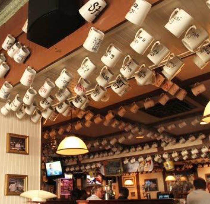 Mug club glasses hang from the ceiling