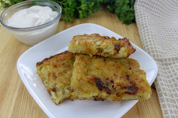 Potato Kugel Cut Into Squares With Sour Cream On The Side.