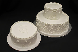 "Photo: Initial wedding cakes featuring last name initial ""G."" 3-dot cluster on side cake & top tier. Swirl & dot border on bottom tier. Tear drop borders."
