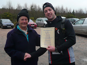 Photo: Brian Ankers, the first person to finish the Slievenamuck Marathon on March 24th, being presented with his certificate by Josephine Tierney, Galtee Walking Club.