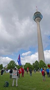 Funkturm, Wiese mit Kundgebungsteilnehmer:innen. Plakat: «BRD raus aus der NATO – NATO raus aus der BRD».