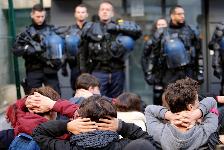 High school students kneel in front of French riot police as they attend a demonstration to protest against the French government's reform plan, in Marseille, France, on December 11, 2018. Picture: REUTERS/JEAN-PAUL PELISSIER