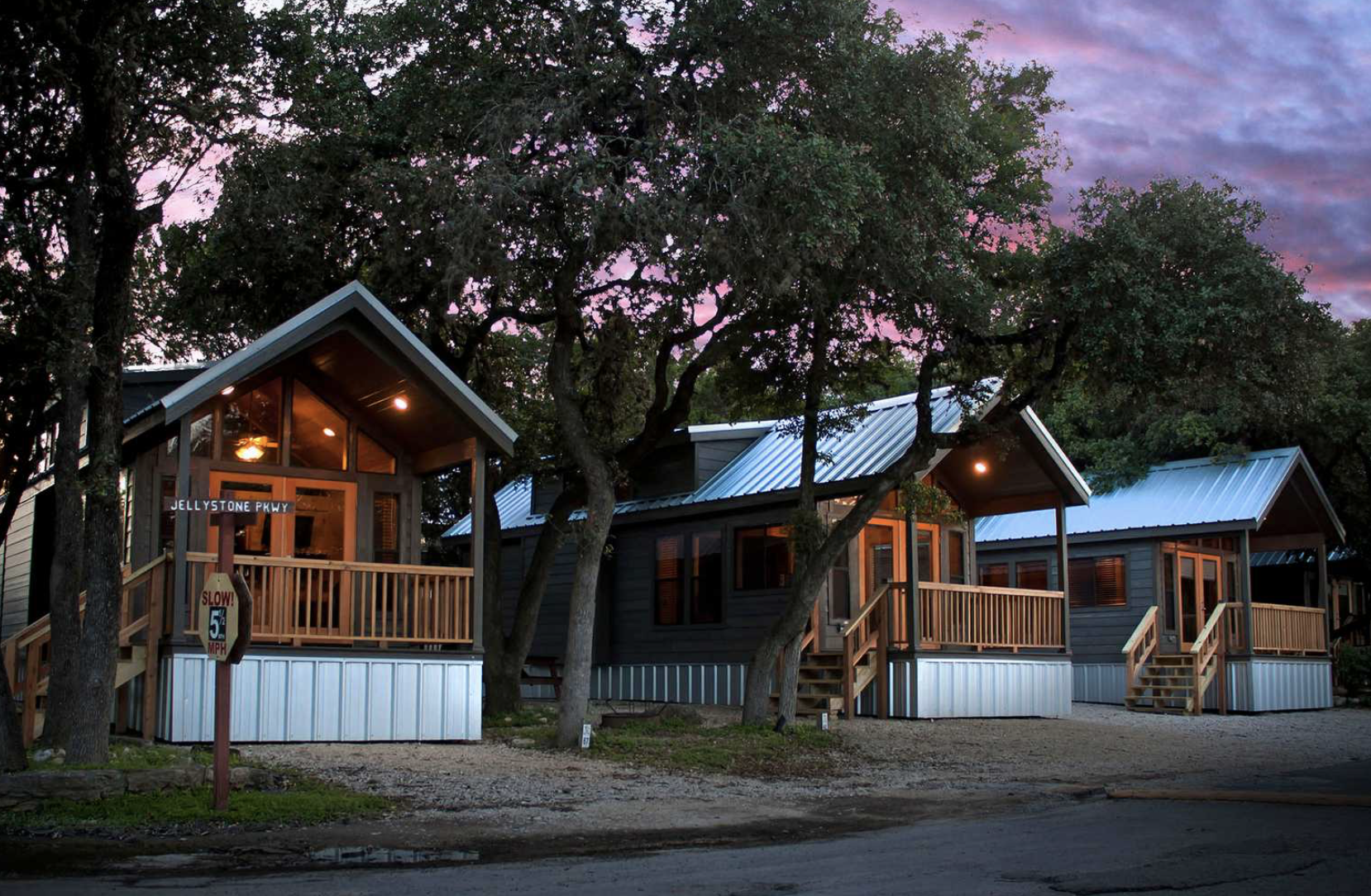 Cabins at sunset with purple sky surrounded by trees