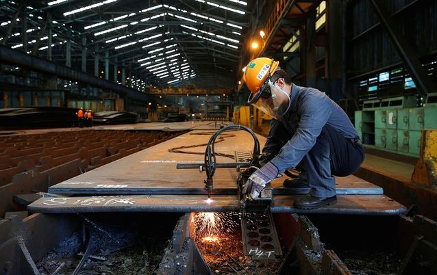 A worker cuts steel plates inside the China Steel Corporation factory, in Kaohsiung, southern Taiwan. Picture: REUTERS