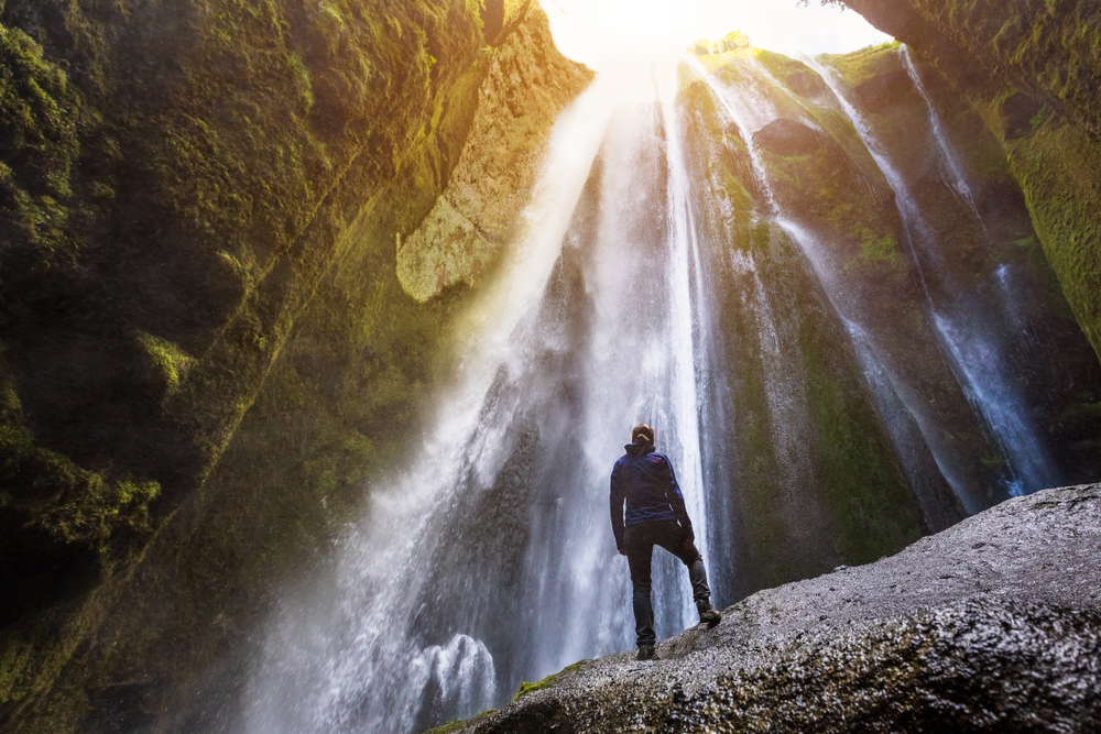 Gljufrabui Canyon in iceland with a hiker standing in front of waterfall falling from above and sunlight shining through