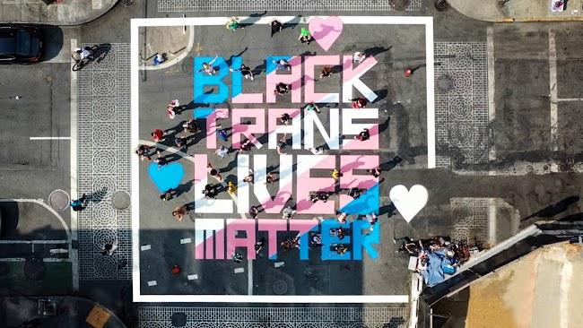 Mural de Black Trans Lives Matters pintado con spray en azul claro, rosa y blanco en intersección de calles.