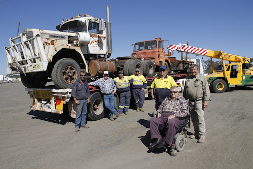 Glen Stoltenberg, Glenn Woods, Andrew Gordon, Max Gordon, front, Lindsay Gordon, left, and crane operator Dennis Hardy, right, with Lex Gordon as the veteran vehicles set off for the National Transport Hall of Fame.