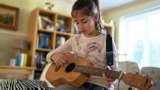 young girl playing guitar