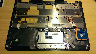 Photo: This is the bottom view of the keyboard bezel, with the SD card reader at lower right and the bottom of the trackpad in the lower middle. Note the metal plates beneath the trackpad.