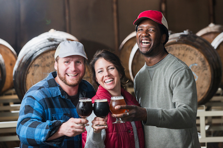 Three people in a microbrewery holding glasses of beer.jpg