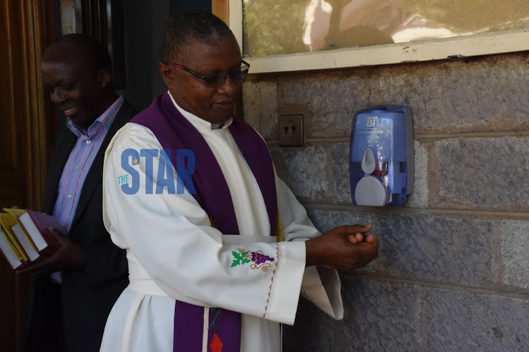 Reverend Gatuma Mbogo sanitising his hands before the service starts at ACK St Marks Church Westlands on March 15,2020
