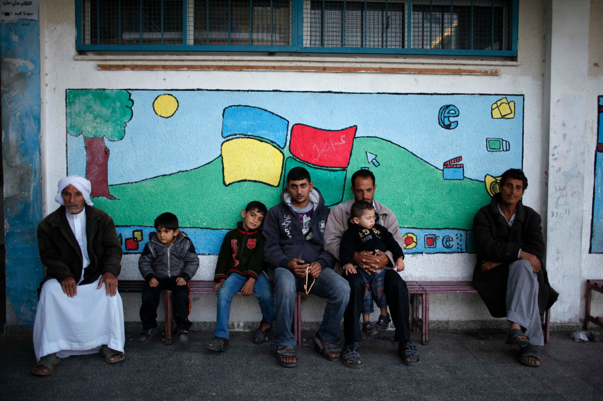Photo: Displaced Palestinians, who fled their houses, sit together as they stay at a United Nations-run school in Gaza City.