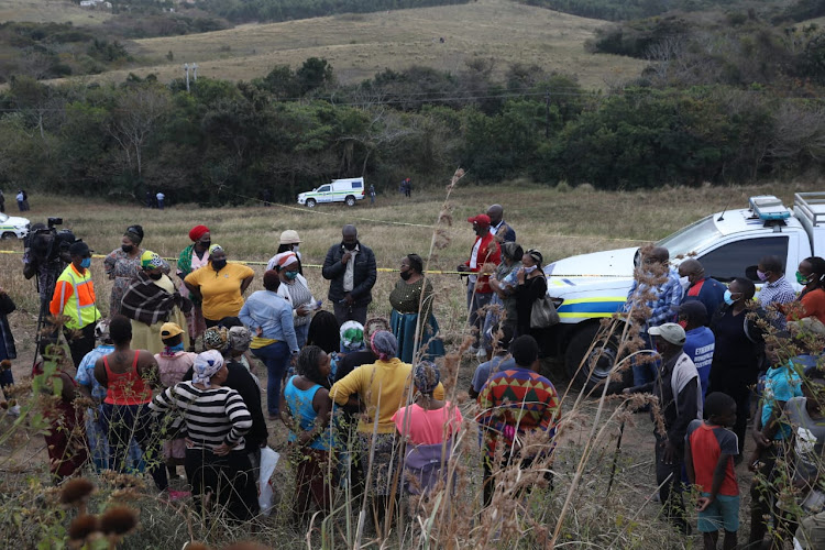 Community members gathered in a sugar cane field where the body of a fifth woman was found on Wednesday.