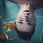 meisje met hoofd half onder water in kom met goudvissen