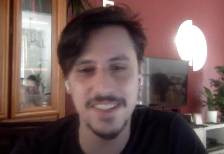 Foto de Fabrício, homem branco, de cabelos curtos e escuros. Ele tem bigode e cavanhaque e está sorrindo. Veste uma camiseta preta.