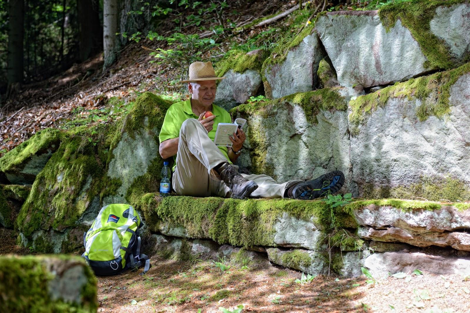 Ein Mann sitzt auf einer Steinbank und genießt eine Pause vom Wandern