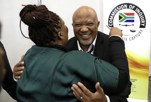 Former deputy minister Mcebisi Jonas gets a hug from former ANC MP Vytjie Mentor at the commission of inquiry into state capture in Johannesburg this week.