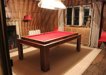 A dark wood elevated pool table with red felt in a loft