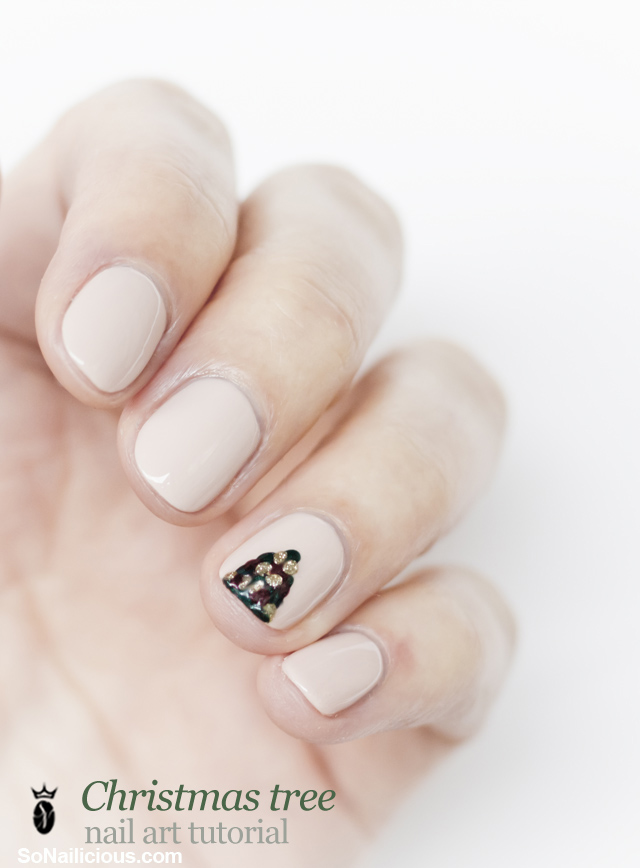 nude nails with one accent nail featuring a tiny Christmas tree